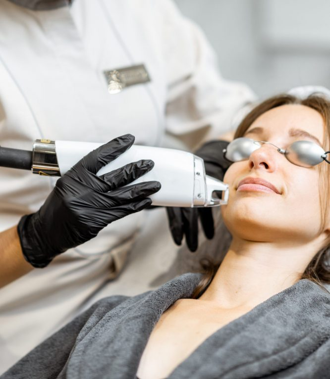 Portrait of a young woman during a facial rejuvenation treatment at medical SPA. LaseMD procedure concept